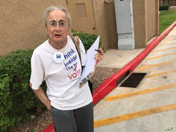 FILE - Rivko Knox, a volunteer with the League of Women Voters, collects signatures, April 19. 2018, for a campaign financing ballot measure outside a polling station in Glendale, Ariz. A judge, Aug. 24, 2018 upheld a 2016 Arizona law that bans group...