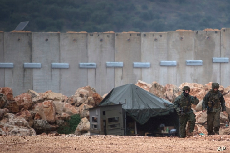 Israeli soldiers, right, serve near the Israel-Lebanon border where the army is digging to look for tunnels from Lebanon in the northern Israeli town of Metula, Dec. 19, 2018.
