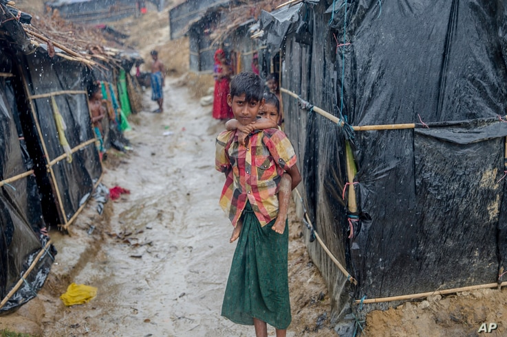 A Rohingya Muslim boy, who crossed over from Myanmar into Bangladesh, holds his brother outside his shelter as it rains in Balukhali refugee camp, Bangladesh, Thursday, Sept. 28, 2017.