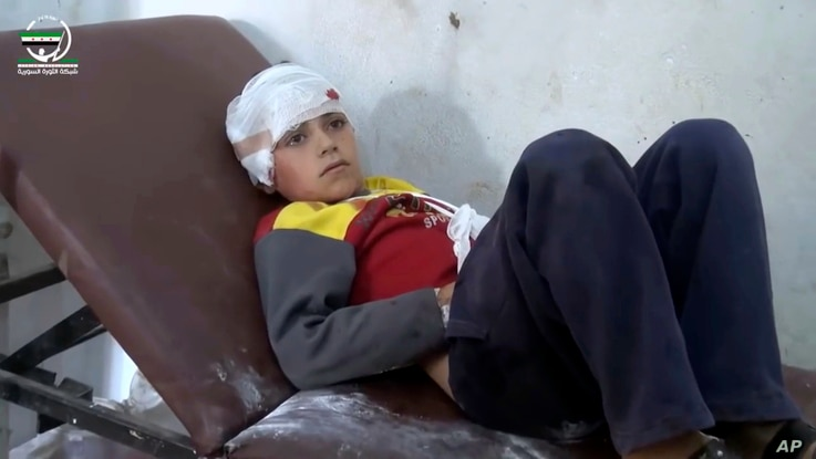 Photo provided by Muaz al-Shami, Syrian Revolution Network, an opposition activist media organization, that is consistent with independent AP reporting, shows a child on a hospital bed, with a bandage around his head after airstrikes killed over 20 p...