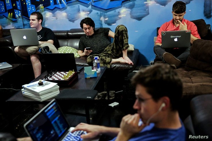 "Zander Dejah (2nd L), 25, who works as a Virtual Reality engineer, Nick Olszowy (C), 25, a software engineer and Andrew Bresee, 26, a software engineer, all who are residents of The Negev tech house, use their electronics during a Sunday ""family"" din..."