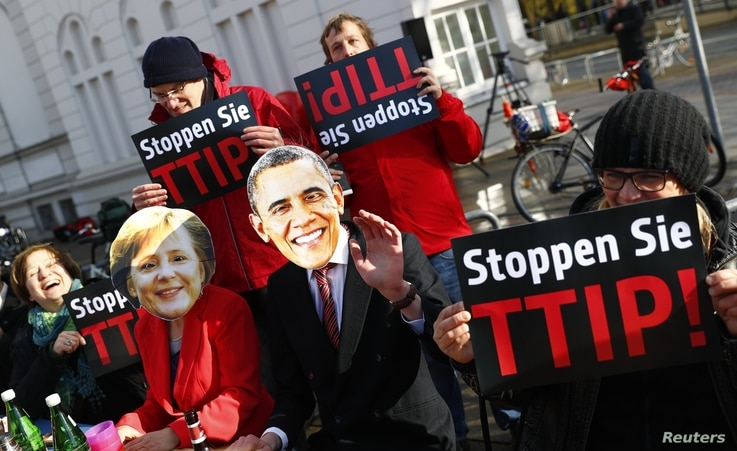 Protesters wear masks of U.S. President Barack Obama and German Chancellor Angela Merkel as they demonstrate against the Transatlantic Trade and Investment Partnership (T-TIP) free trade pact at the Hannover Messe in Hannover, Germany, April 24, 2016...