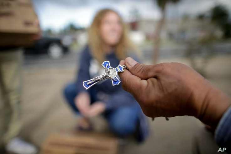 FILE - Marcelo Perez (R), an undocumented migrant from Mexico, shows his cross to volunteers dispensing donated goods to day laborers alongside a hardware store, Feb. 4, 2017, in San Diego, California.