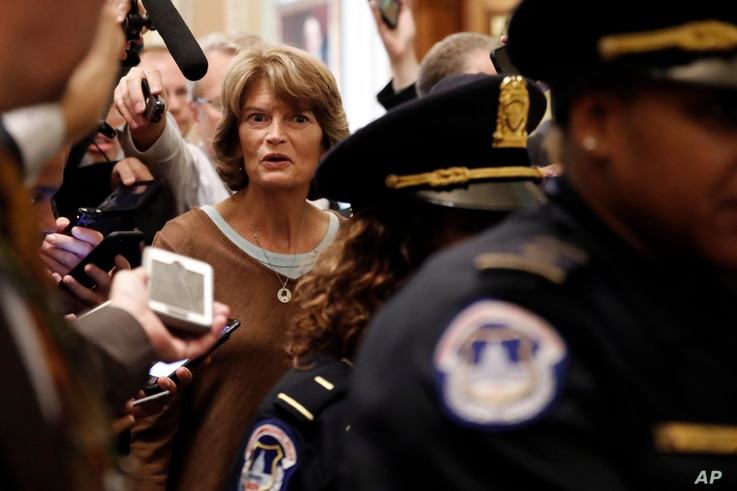 Sen. Lisa Murkowski, R-Alaska, is surrounded by reporters asking questions about Supreme Court nominee Brett Kavanaugh, Friday Sept. 28, 2018, on Capitol Hill in Washington. After a flurry of last-minute negotiations, the Senate Judiciary Committee a...