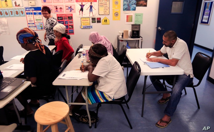Syrian refugee Ahmad Alabood, right, sits in the back row during English class at Della Lamb Community Services in Kansas City, Mo., on June 13, 2016.
