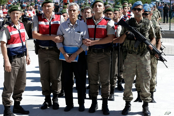 Paramilitary police and members of the special forces escort former Air Force commander Akin Ozturk and other suspects of last year's failed coup, outside the courthouse at the start of a trial, in Ankara, Turkey, Tuesday, Aug. 1, 2017.