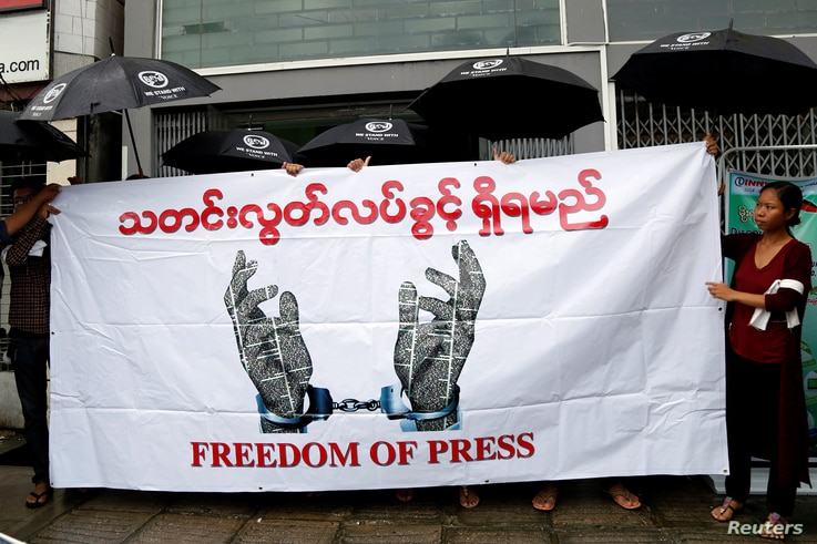 FILE - Journalists hold a banner as they protest against a law they say curbs free speech in Yangon, Myanmar, June 8, 2017.