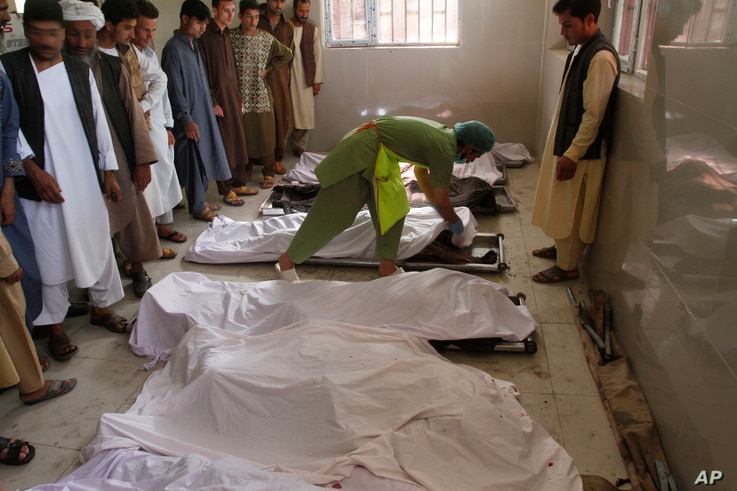 FILE - Men mourn over relatives' bodies in a hospital near the site of an explosion in Herat, Afghanistan, Jun 6, 2017.
