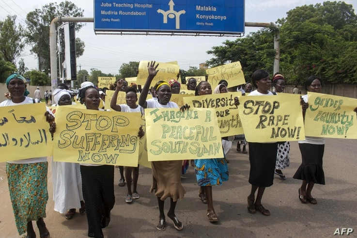 FILE - Women march carrying placards with messages demanding peace and their rights, on the streets of South Sudan's capital, Juba, July 13, 2018.
