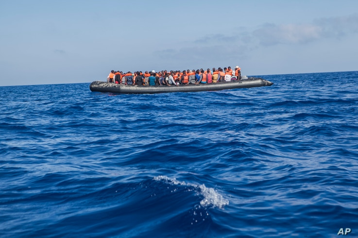A rubber boat with 129 migrants on board, among them 60 women, is seen sailing out of control about 15 miles north of Al Khums, Libya, Aug. 1, 2017.