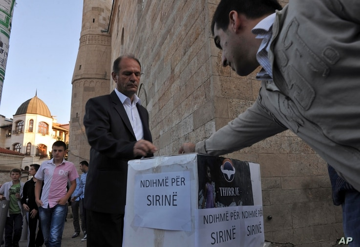 """FILE - Kosovo Muslims donate money in a box labeled """"Help for Syria"""" in front of the Grand Mosque in Kosovo's capital Pristina in this 2012."""