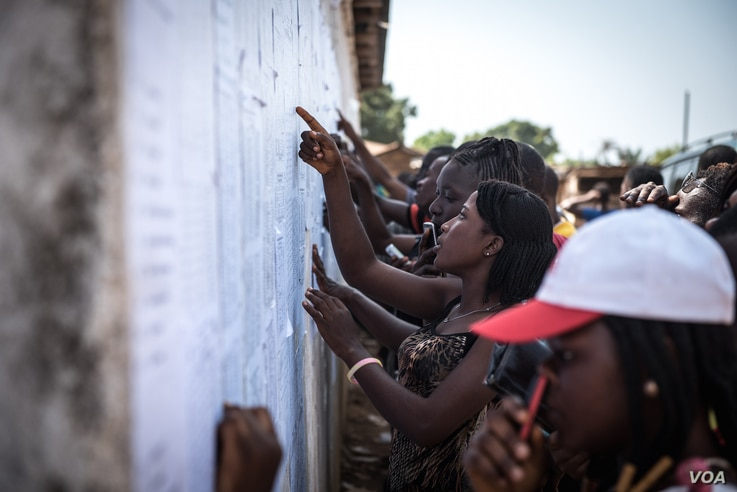 Youth check lists of names to see if they were selected as poll workers for the upcoming general elections in Port Loko, Sierra Leone,  March 3, 2018. Youth unemployment is a chronic challenge in the West African nation. (J. Patinkin/VOA)