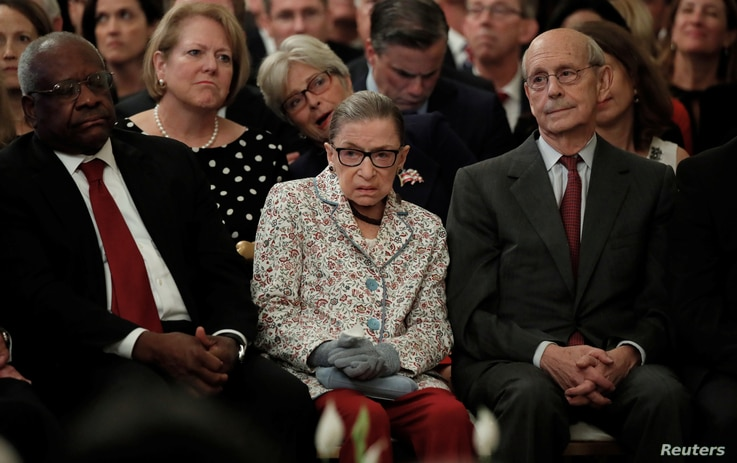 U.S. Supreme Court Associate Justices, from left, Clarence Thomas, Ruth Bader Ginsburg and Stephen Breyer watch from the front row as Brett Kavanaugh takes his ceremonial oath of office while participating in a ceremonial public swearing-in in the Ea...