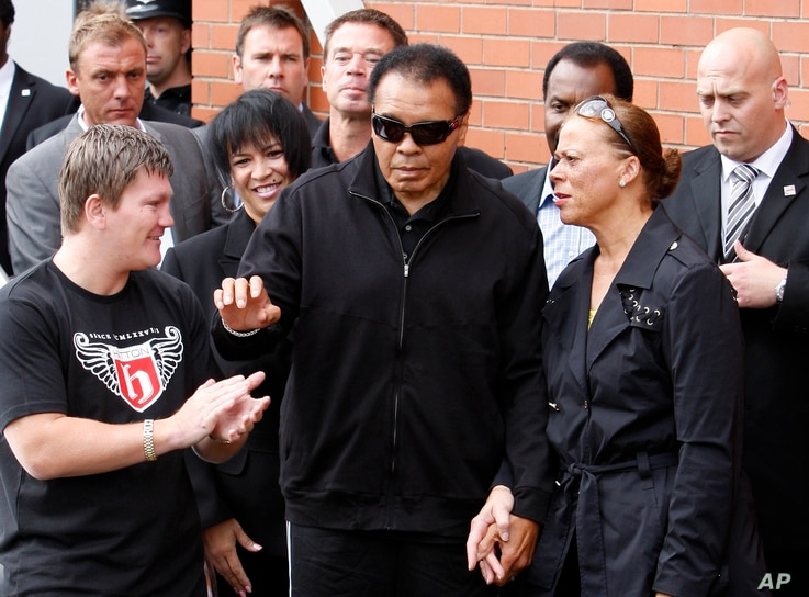 Boxing legend Muhammad Ali, centre, gestures to fans as he arrives for a visit to boxer Ricky Hatton's, seen pictured left, gym, Manchester, England, Wednesday, Aug. 26, 2009.