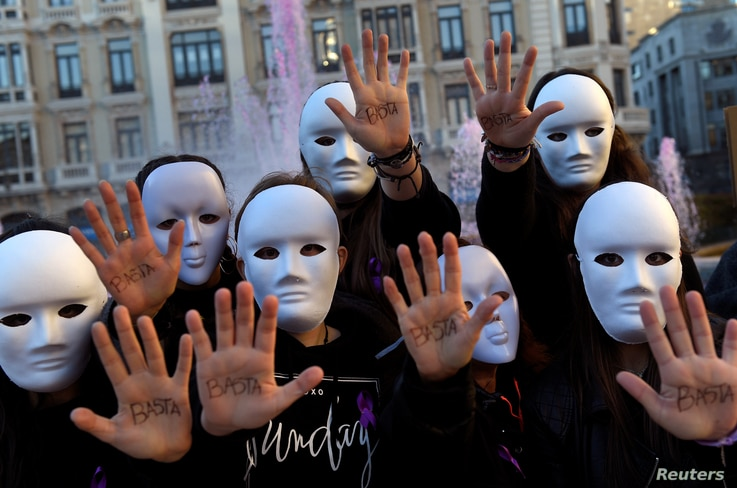 """Students wearing masks pose with the word """"Enough"""" written on their hands during a performance to commemorate victims of gender violence, during the U.N. International Day for the Elimination of Violence against Women, in Oviedo, Spain Nov. 25, 2016...."""