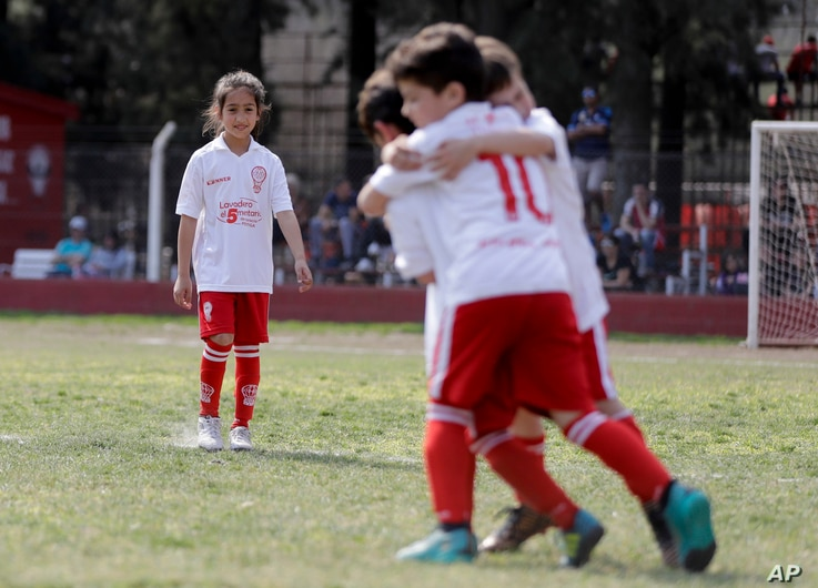 """In this Sept. 8, 2018, photo, Candelaria Cabrera, right, watches her soccer teammates celebrate a goal against Alumni in Chabaz, Argentina. """"Cande,"""" as she is known by friends and family, is the only girl playing in a children's soccer league in th..."""