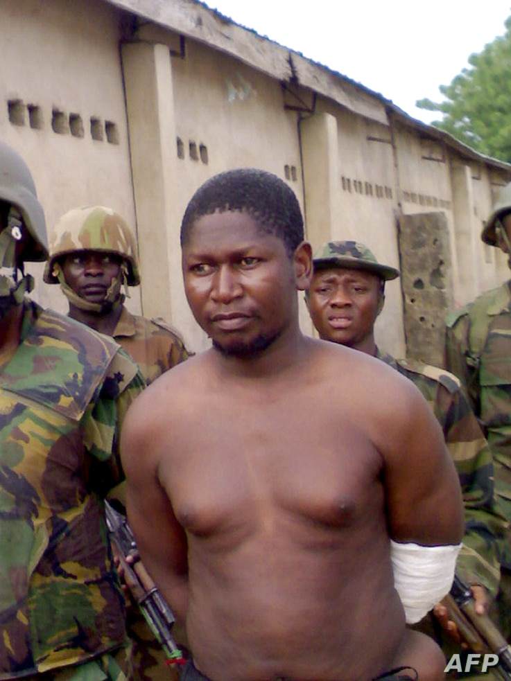 FILE - Handout photo obtained on August 5, 2009 shows the leader of the Boko Haram Islamic sect Mohammed Yusuf, 39, surrounded by soldiers at Giwa Barracks in Maiduguri, northeastern Nigeria, on July 30, 2009 shortly after his capture by Nigerian tro...