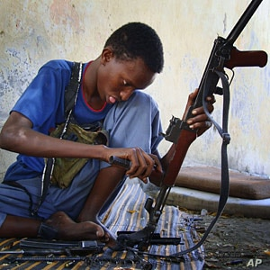 Somali fighter loads and cleans AK-47