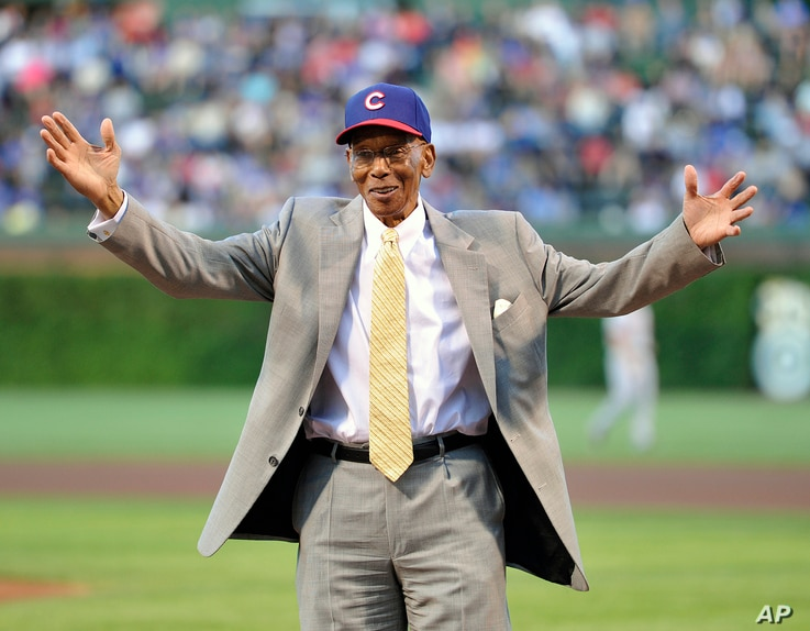 Former Chicago Cubs first baseman Ernie Banks waves to the crowd before the Cubs' baseball game against the Cincinnati Reds, Aug. 13, 2013, in Chicago.