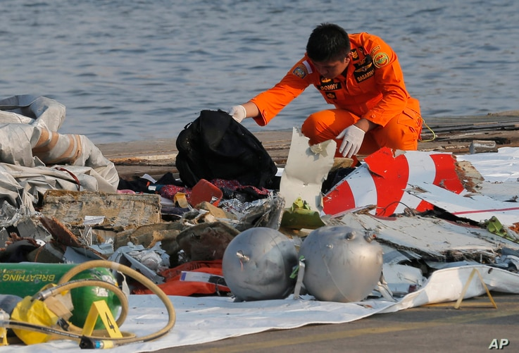 A member of Indonesian Search and Rescue Agency (BASARNAS) inspects debris believed to be from Lion Air passenger jet that crashed off Java Island at Tanjung Priok Port in Jakarta, Indonesia, Oct. 29, 2018.