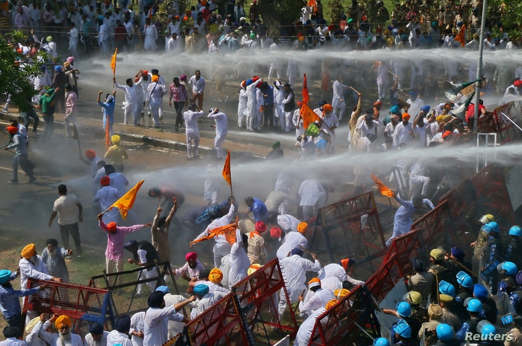 Demonstrators are hit by police water cannon during a protest, organized by Punjab's main opposition party Shiromani Akali Dal, demanding debt waiver of farmers in Chandigarh, India, March 20, 2018.