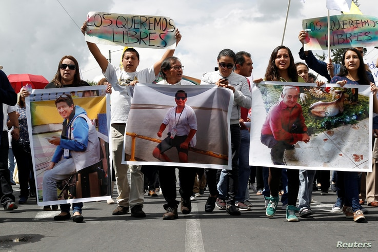 FILE - Relatives and friends hold pictures of Ecuadorean photojournalist Paul Rivas, left, journalist Javier Ortega, center, and their driver Efrain Segarra, who were kidnapped near the Colombian border, during a protest march to demand for their rel...