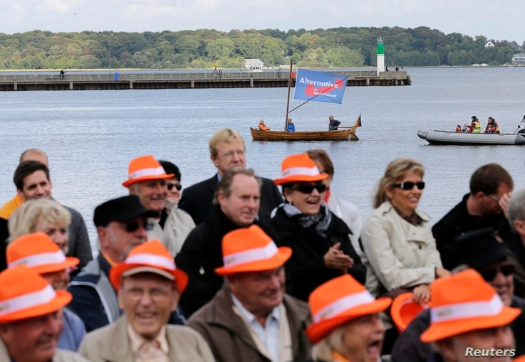 Supporters of the anti-euro party, the Alternative for Germany (AfD) sail a boat next to the square where German Chancellor and conservative Christian Democratic Union (CDU) leader Angela Merkel is holding a CDU election campaign rally in Stralsund, ...
