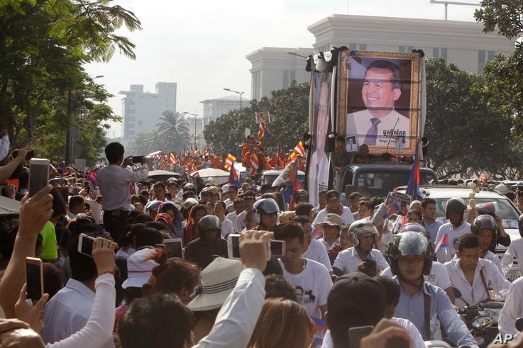 Cambodia mourners take photos as they watch the funeral procession for Cambodian leading government critic Kem Ley, whose portraits are displayed on a vehicle, in Phnom Penh, July 24, 2016.
