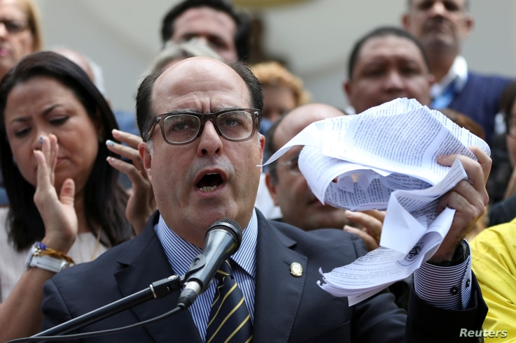 Julio Borges, president of Venezuela's National Assembly, waves a torn copy of the Supreme Court's decision at a news conference in Caracas, Venezuela, March 30, 2017.