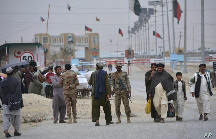 Pakistani paramilitary soldiers stand guard while people wait for opening border crossing, in Chaman, Pakistan, March 20, 2017.