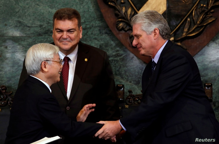 Vietnam's Communist Party Secretary, General Nguyen Phu Trong, shakes hands with Cuba's First Vice-President Miguel Diaz-Canel, next to Gustavo Cobreiro, rector of the University of Havana, in Havana, Cuba, March 29, 2018.