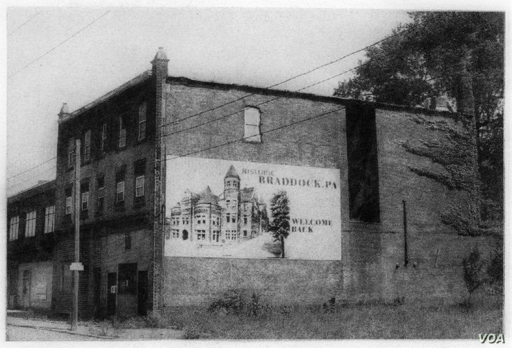 This building, with a banner welcoming people to historic Braddock, Pennsylvania, has spraypaint on the front door indicating it is scheduled to be torn down, which it was after this image was taken. (George L. Smyth)