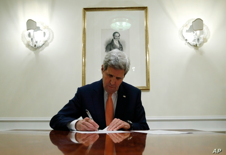 US Secretary of State John Kerry signs a series of documents in Vienna, Austria, Saturday Jan. 16, 2016.