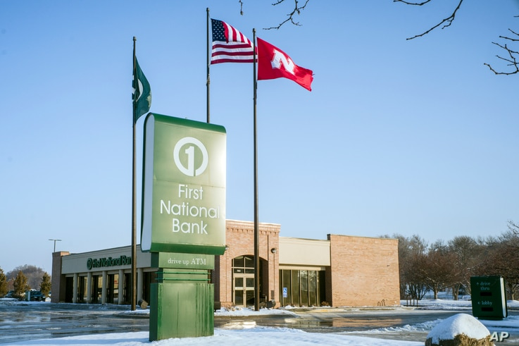Flags fly over a First National Bank branch in Omaha, Neb., Feb. 23, 2018. The Nebraska-based First National Bank of Omaha said Thursday it will not renew its contract to issue the National Rifle Association Visa Card, spokesman Kevin Langin said in ...