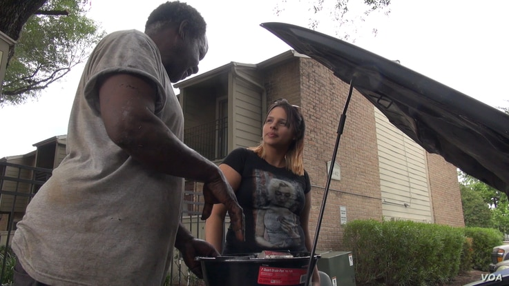 A mechanic named Jerry has been helping his neighbors clean out their flooded vehicles in hopes that he can get them to start, but he said many of them will be a total loss if the water damage is extensive. (G. Flakus/VOA)