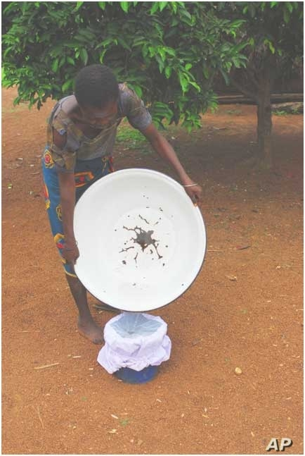 Aug. 17, 2005. Nigeria. A Nigerian adolescent demonstrates one technique used for filtering water to remove water fleas that carry Guinea worm larva. The Carter Center assists the Nigerian Ministry of Health in distributing water filters to protect p...