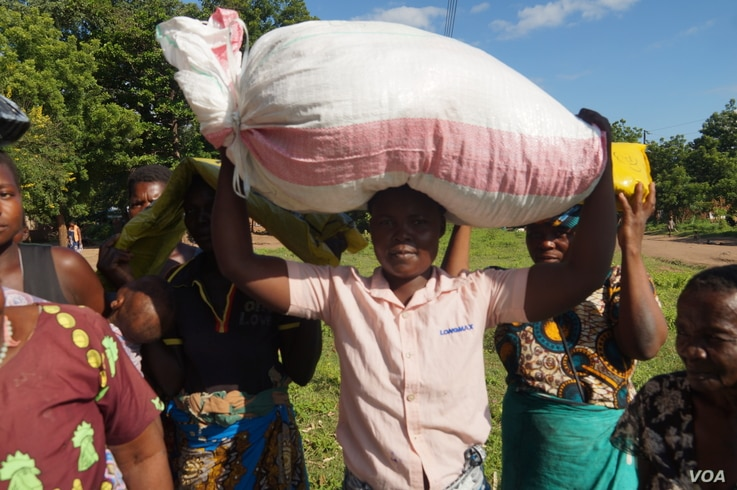 Flood Victims in Chikwawa district carry a bag of maize meant to be shared among themselves. (L. Mesina for VOA)