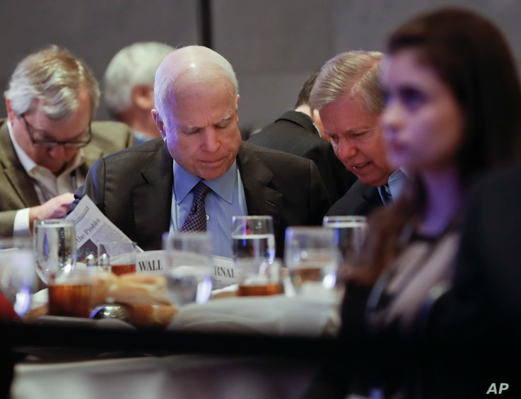 Sen. John McCain, R-Ariz., left, and Sen. Lindsey Graham, R-S.C., right, read the Wall Street Journal newspaper as they wait for President Donald Trump to speak to House and Senate GOP lawmakers at the annual policy retreat in Philadelphia, Jan. 26, ...
