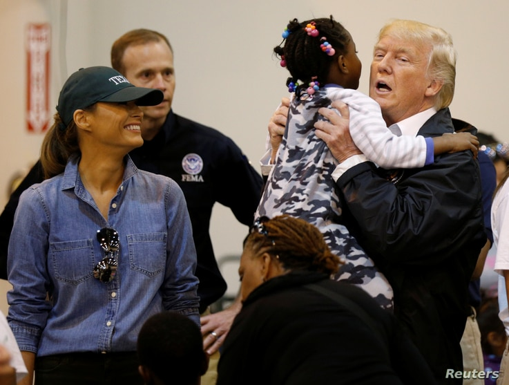 U.S. President Donald Trump lifts up a little girl as he and first lady Melania Trump visit with flood survivors of Hurricane Harvey at a relief center in Houston, Texas, Sept. 2, 2017.