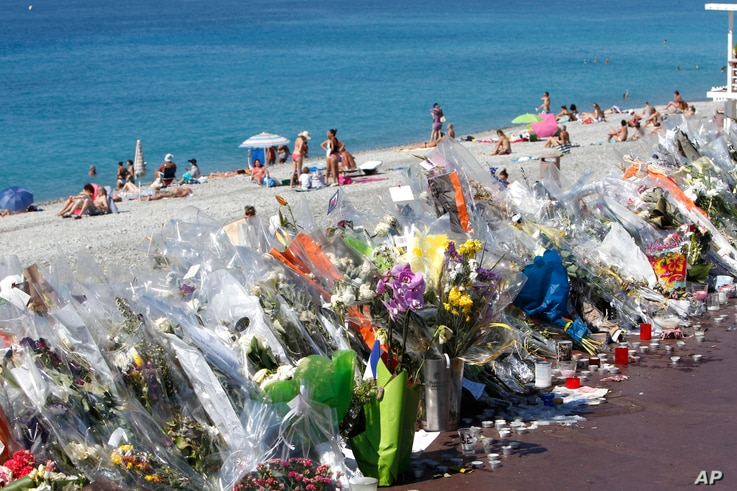 FILE - Flowers and messages are placed along the beach of the Promenade des Anglais in Nice, southern France,  July 20, 2016.