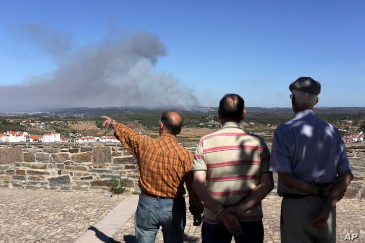 Men in Abrantes, central Portugal, watch a forest fire burning on the hills outside the city, Aug.11, 2017.