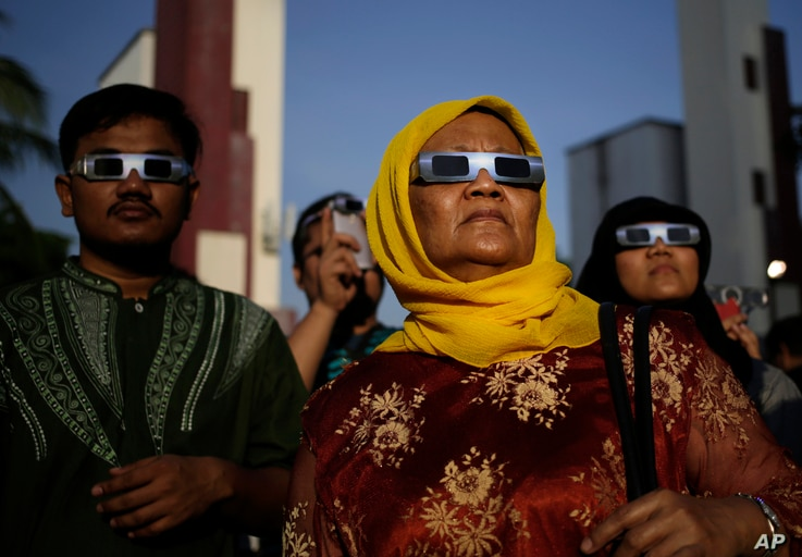 People look up at the sun wearing protective glasses to watch a solar eclipse in Jakarta, Indonesia, Wednesday, March 9, 2016.