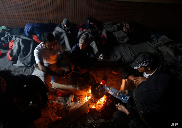 Migrants gather around a fire used for cooking and warmth in an abandoned brick factory in the northern Serbian town of Subotica, Feb. 8, 2017.