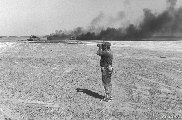 Israeli Major General Ariel Sharon watches an aerial drop through his binoculars in the Sinai Peninsula, then occupied by Israel, during the Middle East War, June 8, 1967.