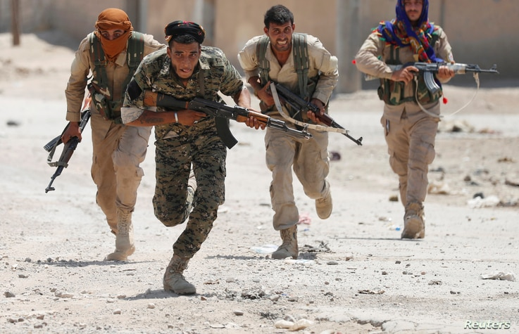 Kurdish fighters from the People's Protection Units (YPG) run across a street in Raqqa, Syria, July 3, 2017.