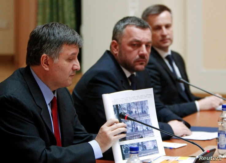 Ukraine's Interior Minister Arsen Avakov speaks and shows documents of an investigation as acting Attorney General Oleh Makhnitsky and Chief of the Security Service of Ukraine (SBU) Valentyn Nalyvaichenko (L-R) listen in Kyiv, April 3, 2014.