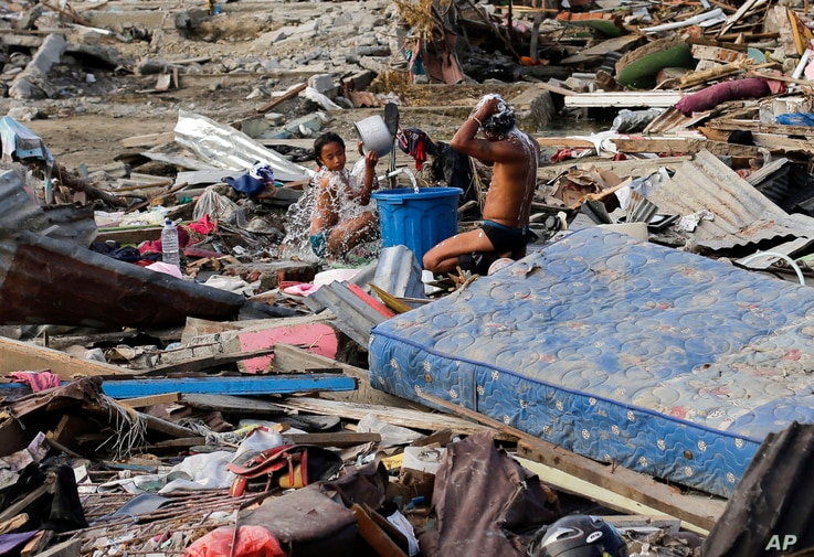 Residents take a bath amid remains of toppled homes and structures at the earthquake and tsunami-hit Palu, Central Sulawesi, Indonesia, Oct. 5, 2018.