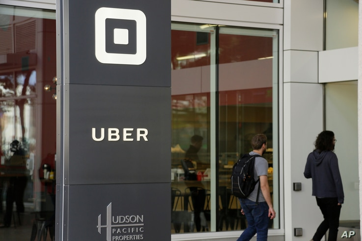 People make their way into the building that houses the headquarters of Uber, June 21, 2017, in San Francisco.