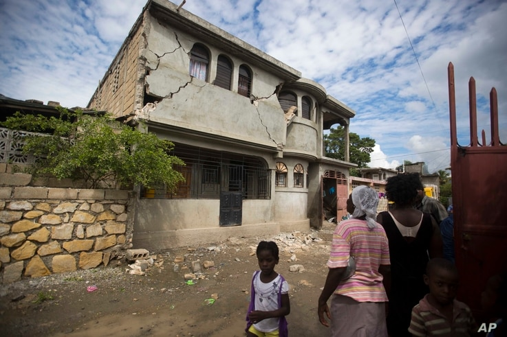 Residents look at a home damaged by a magnitude 5.9 earthquake the night before, in Gros Morne, Haiti, Oct. 7, 2018.