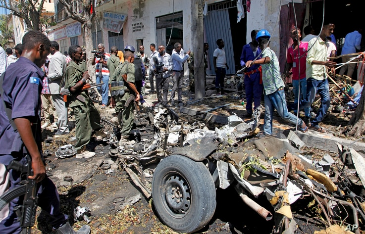 APTOPIX Somalia ViolenceSecurity forces and others inspect the scene of a car bomb attack in the capital Mogadishu, Somalia Monday, April 11, 2016.